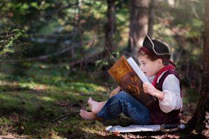 Oak Meadow boy in a pirate costume reading