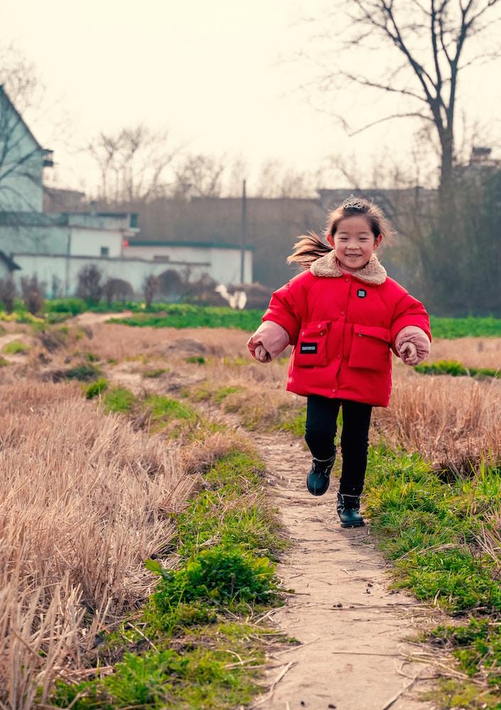 Oak Meadow homeschool student running in red jacket